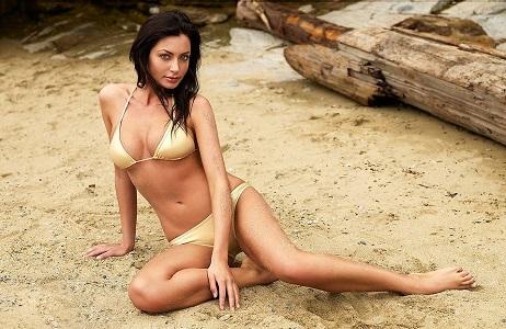 """Bodog.com, """"A beautiful brunette in a bikini posing at the beach"""", CC BY 2.0"""
